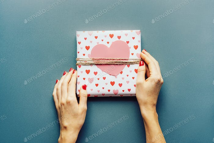 Top view of female hands holding a wrapped gift with a large paper hear