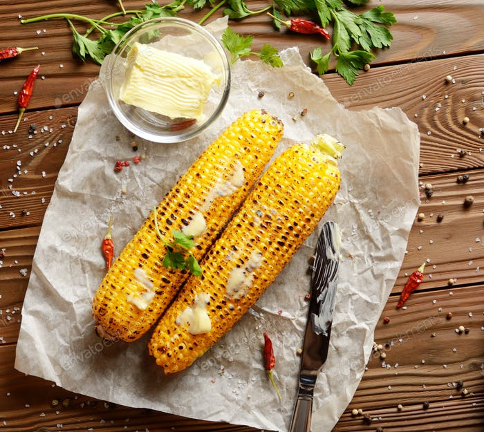 Top view of kitchen table with flat lay grilled sweet corn cob u