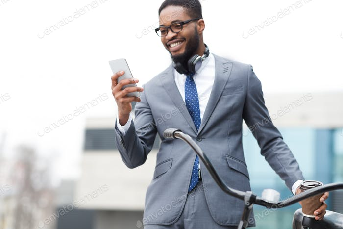 Happy afro entrepreneur using phone, standing with bicycle outdoors