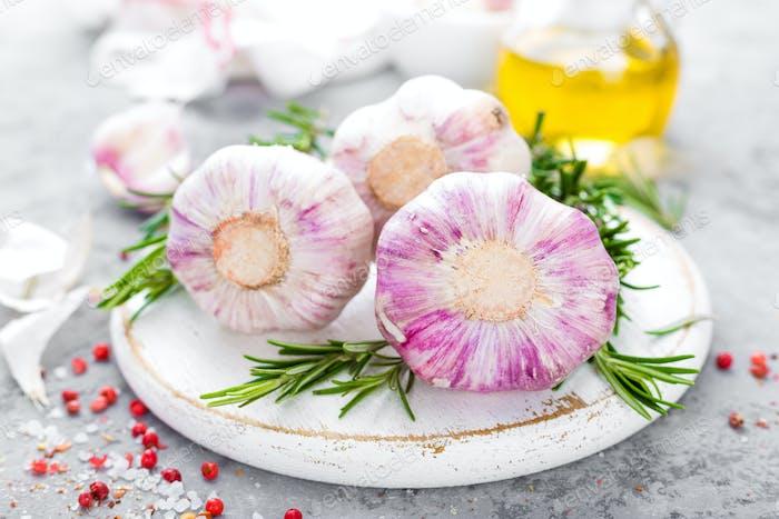 Knoblauch. Frischer Knoblauch, Öl und Rosmarin auf Küchentisch