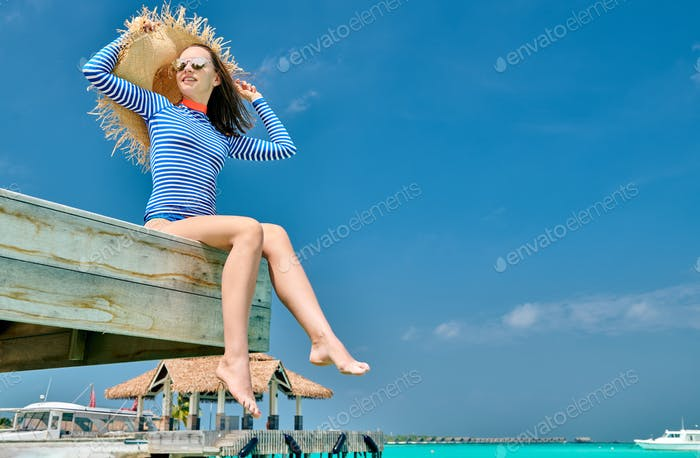 Woman sitting at beach jetty