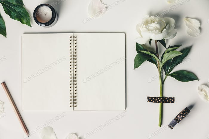 Flat-lay of Beautiful peony flower taped on white background and open notebook