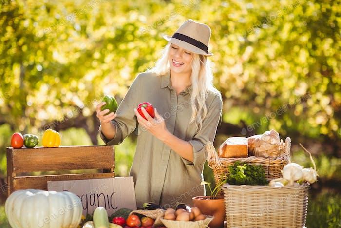 Blonde hält frische Paprika über einen Tisch der lokalen Küche