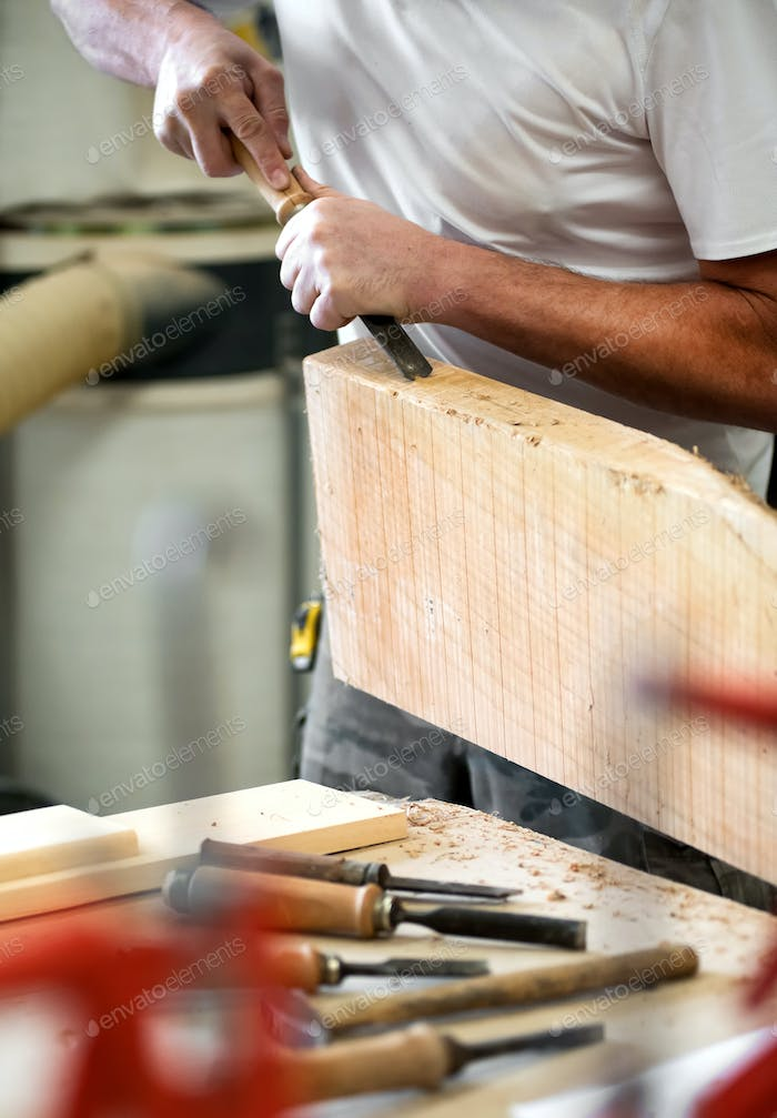 Carpenter working on a block of wood with a chisel