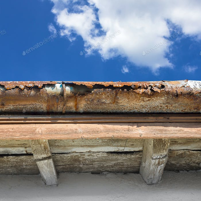 Old gutter against blue sky