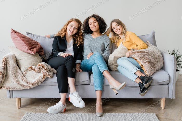 Happy restful girls in casualwear relaxing on couch at home