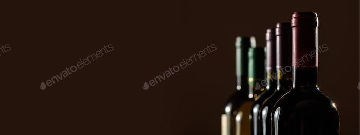Wine bottles on black background, copy space