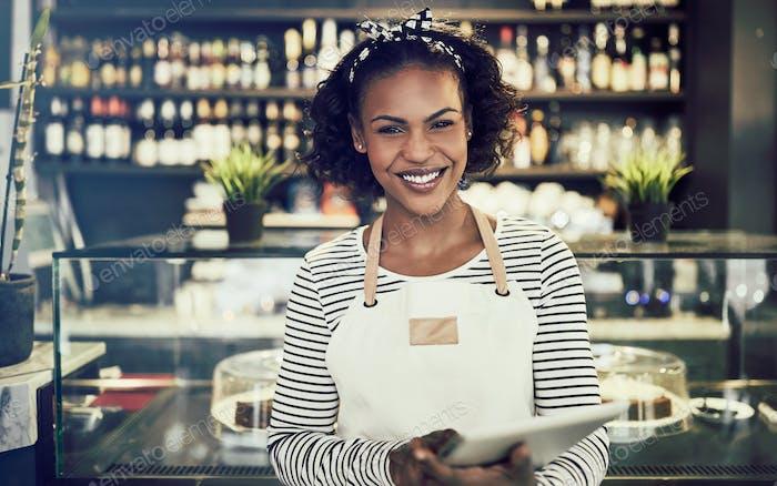 Smiling entrepreneur standing in her cafe using a digital tablet