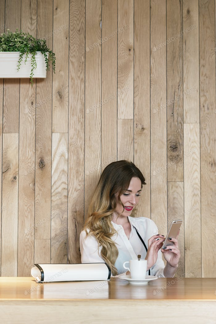 Elegant businesswoman writing text with a smartphone in a restaurant