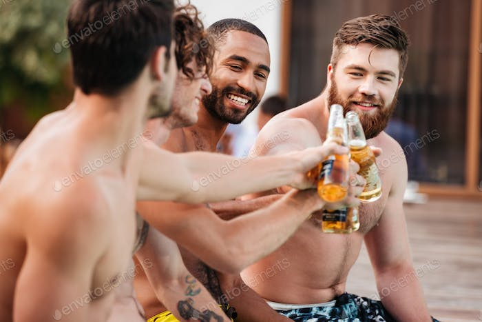 Handsome young smiling men having fun in swimming pool
