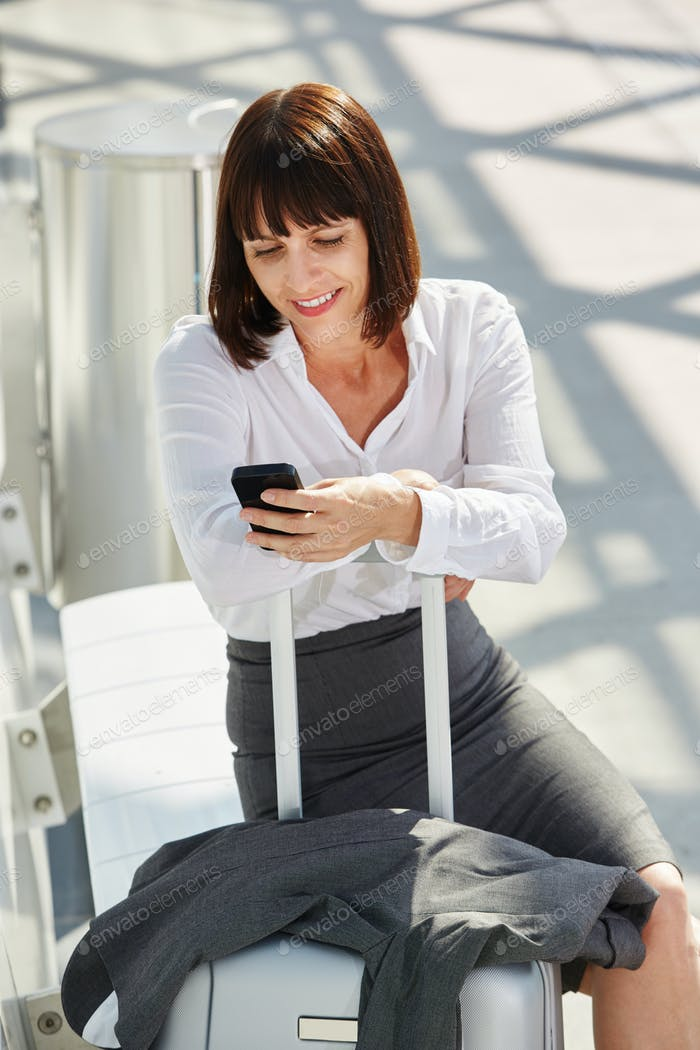 business woman traveler waiting with phone and suitcase