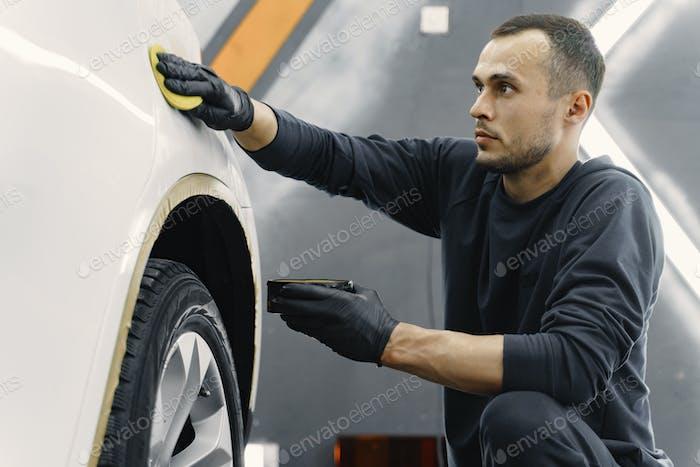 Человек полировать машину в гараже