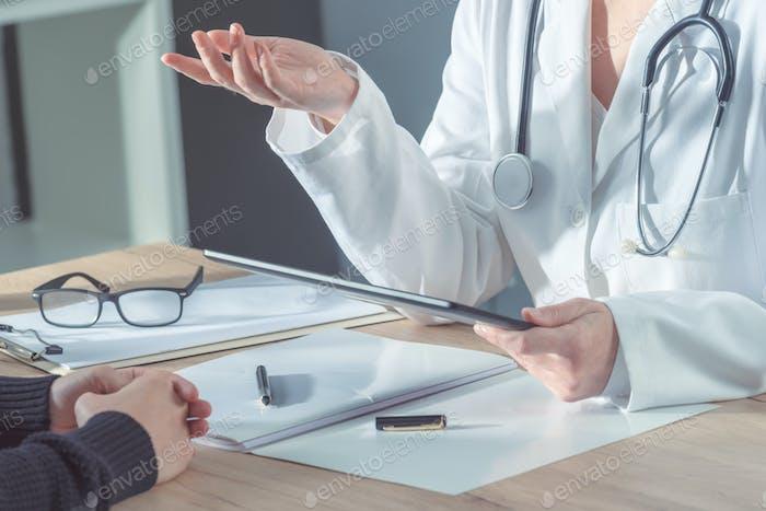 Arzt berät Patienten im Krankenhausbüro