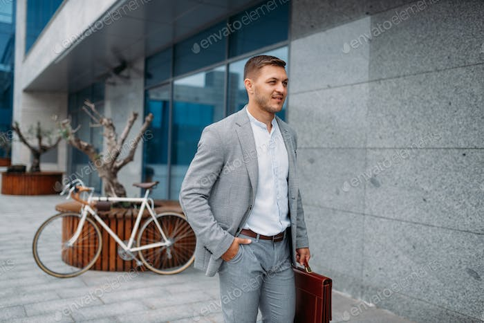 Smiling businessman with bicycle at glass building