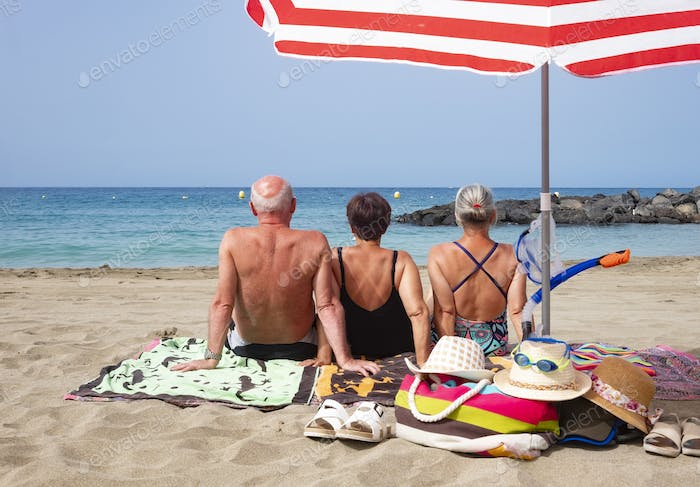 Rear view of three people friends enjoying together holidays at the beach sitting on the sand