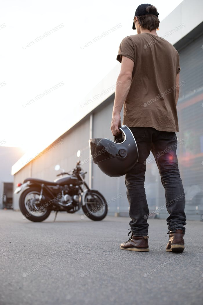 biker guy in front of classic style motorcycle