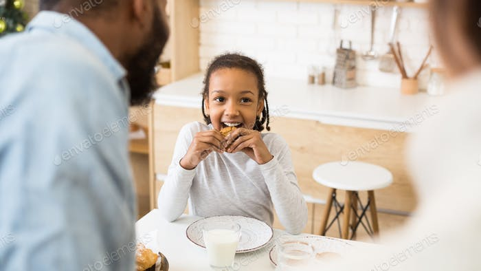 Cute afro girl prefer cookies instead of milk for breakfast