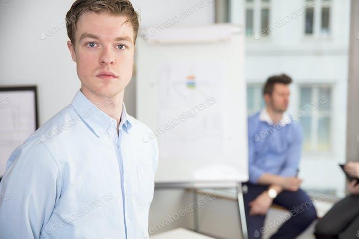 Уверенный молодой бизнесмен, стоящий в офисе
