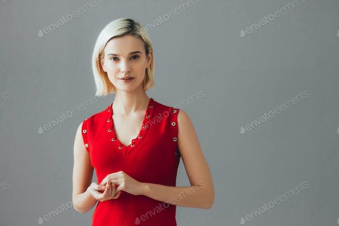Хорошая женщина в красном платье блондинка короткие волосы. Мода женский портрет милая милая девушка