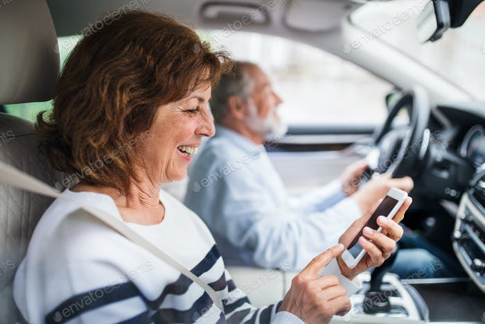 Happy senior couple with smartphone sitting in car, going on trip.