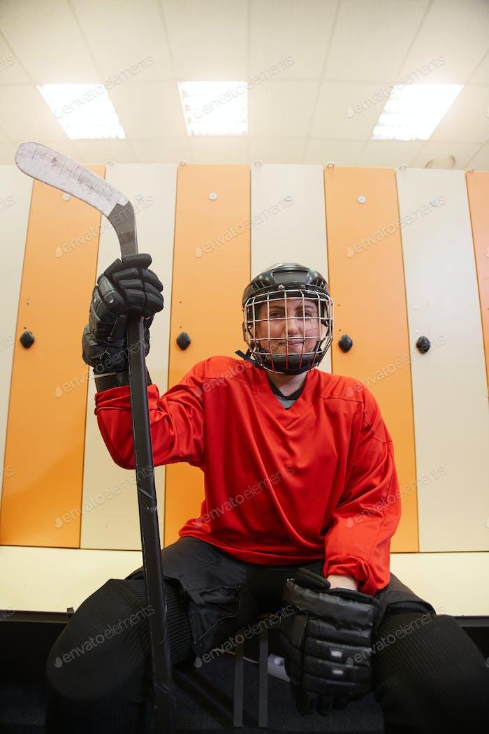 Weibliche Hockeyspieler posiert in Umkleideraum