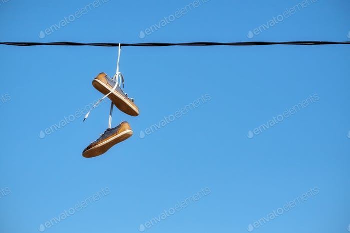 Pair of old shoes hang on power line