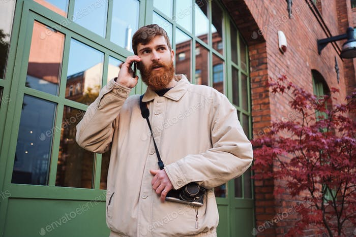 Young casual bearded man intently looking away while talking on cellphone outdoor