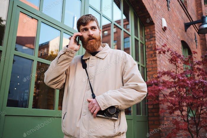 Junge lässig bärtigen Mann aufmerksam Blick weg während im Gespräch auf Handy im freien