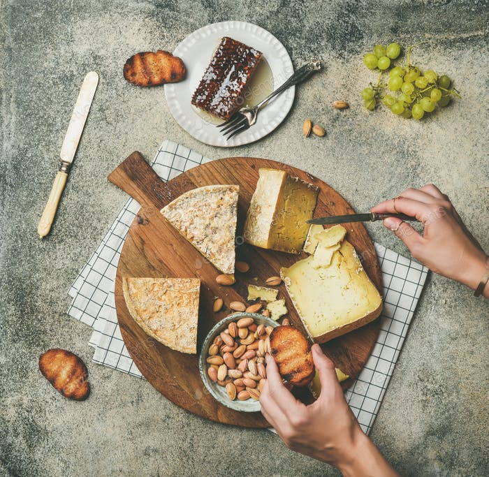 Cheese platter with female hands reaching to food, top view