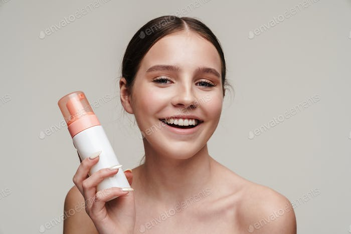 Image of pleased young shirtless woman holding face foam and smiling