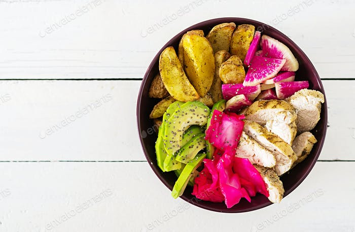 Buddha bowl dish with chicken fillet, beked potato, avocado, cabbage, watermelon radish