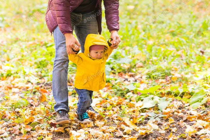 Father and his little son having fun in autumn park
