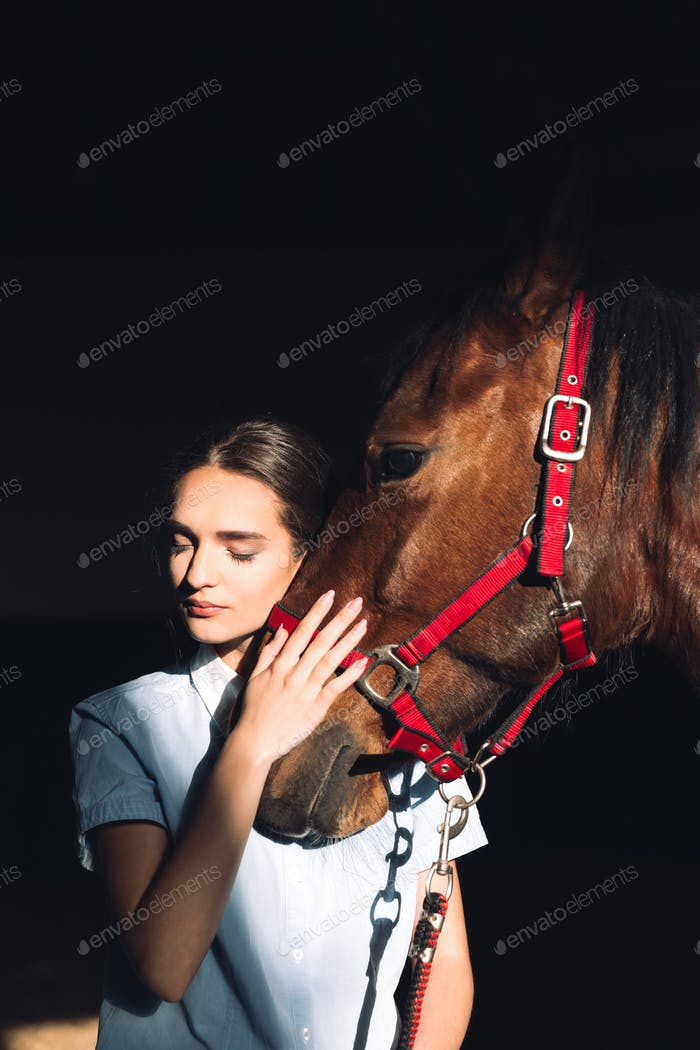 Happy young girl sitting outdoors hugging her horse