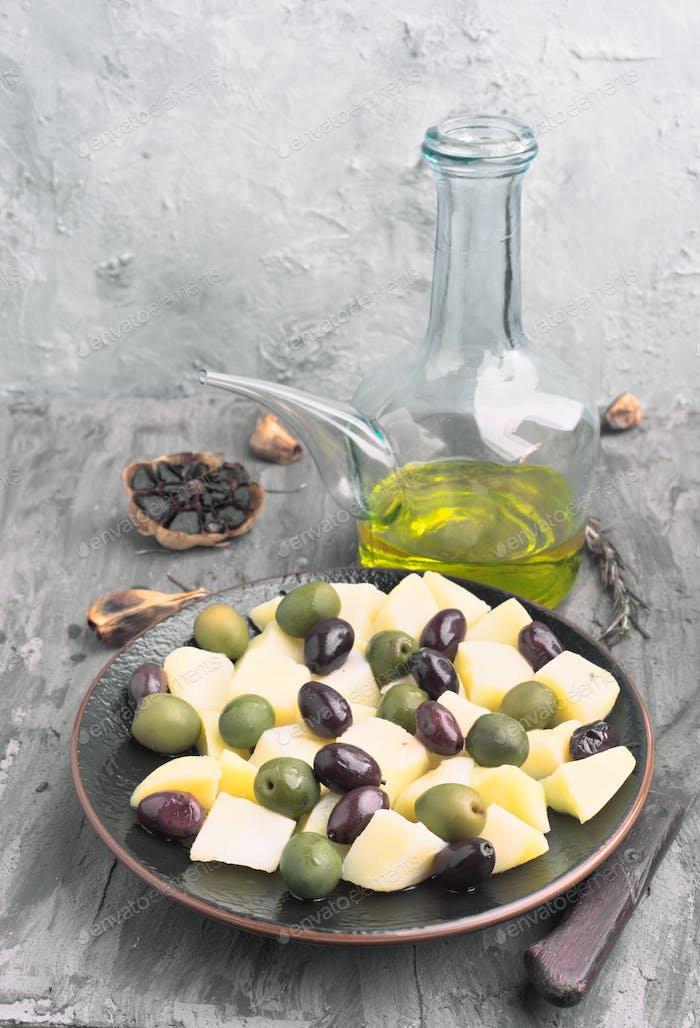 homemade potato salad with green and black olives, in gray rustic setting