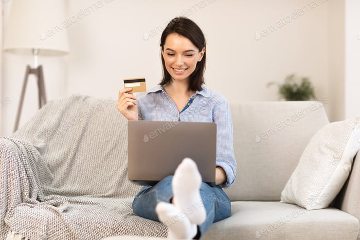 Young woman making purchases sitting on the couch