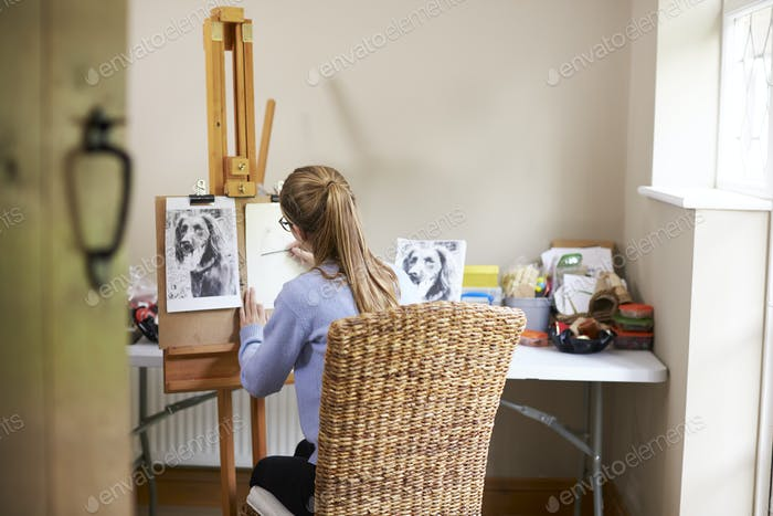 Female Teenage Artist Sitting At Easel Drawing Picture Of Dog From Photograph In Charcoal