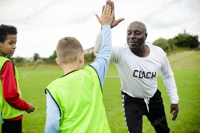 Football-Trainer macht eine hohe fünf mit seinem Schüler