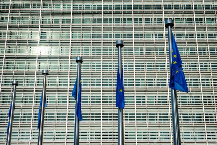 EU European Union flags in front of European Comission building in Background. Brussles, Belgium