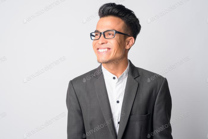 Face of happy young Asian businessman with eyeglasses thinking