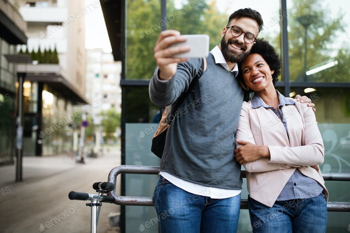 Happy couple having fun and taking a selfie. Smiling people enjoying city life