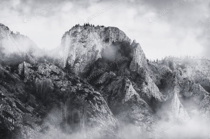 Mountain landscape with fog over cliff