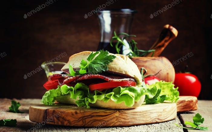 Sandwich mit Schinken, Salat und Tomaten in Weizenbrötchen