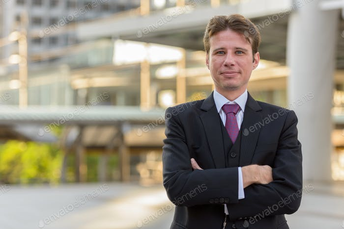 Businessman with arms crossed in front of modern building at Ban