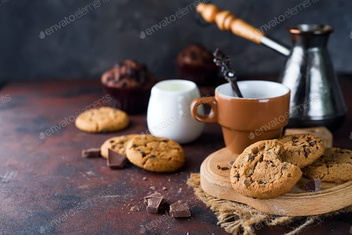 Chocolate cookies in plate and cup of hot coffee on stone table