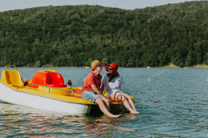 Portrait of young couple in love talking while pedal boating on the lake.