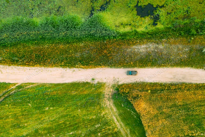 Aerial View Of Car SUV Parked On Countryside Road Between Rural Field And Marsh Bog Swamp Landscape