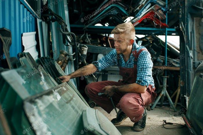 Male repairman choosing glass on car junkyard