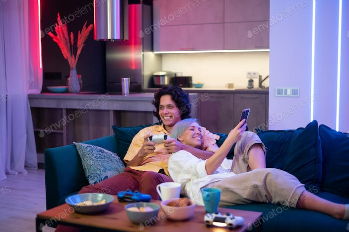Young woman spending time with her boyfriend at home. She using smart phone while he is playing