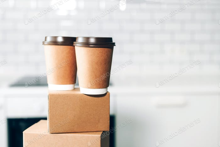 Craft paper cups with coffee to go and food box, lunch on tabletop over white kitchen. Banner, copy