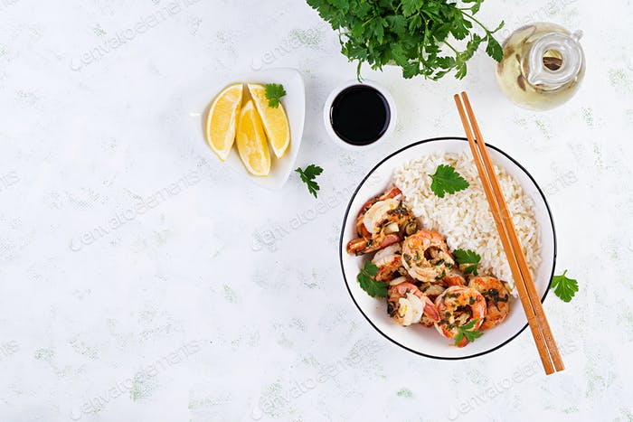 Gegrillte Garnelen und gekochter Reis. Königsgarnelenschwänze in Orangen-Knoblauch-Sauce mit Petersilie.